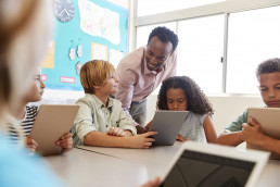 african american teacher overseeing four students using tablets in a classroom