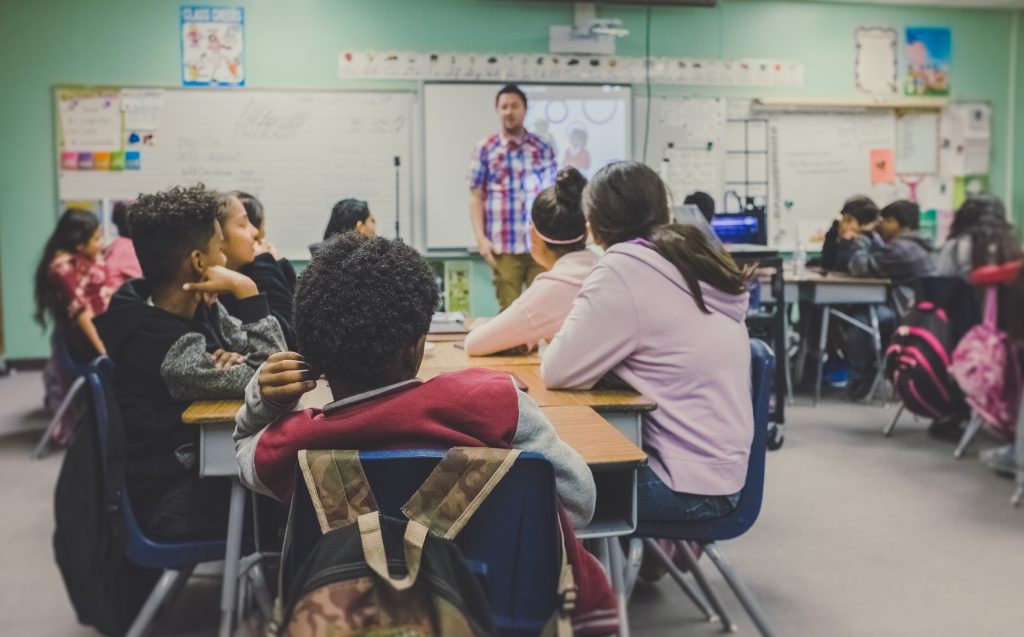 Adult man teaching a classroom of students