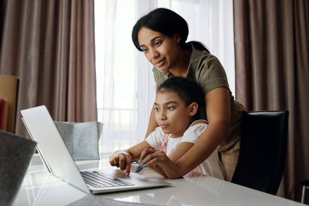 mom helping child on computer